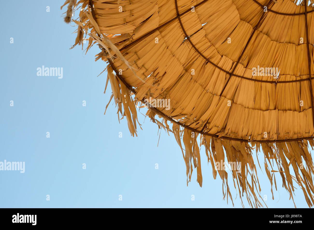 straws of straw umbrella against the blue sky - Stock Image