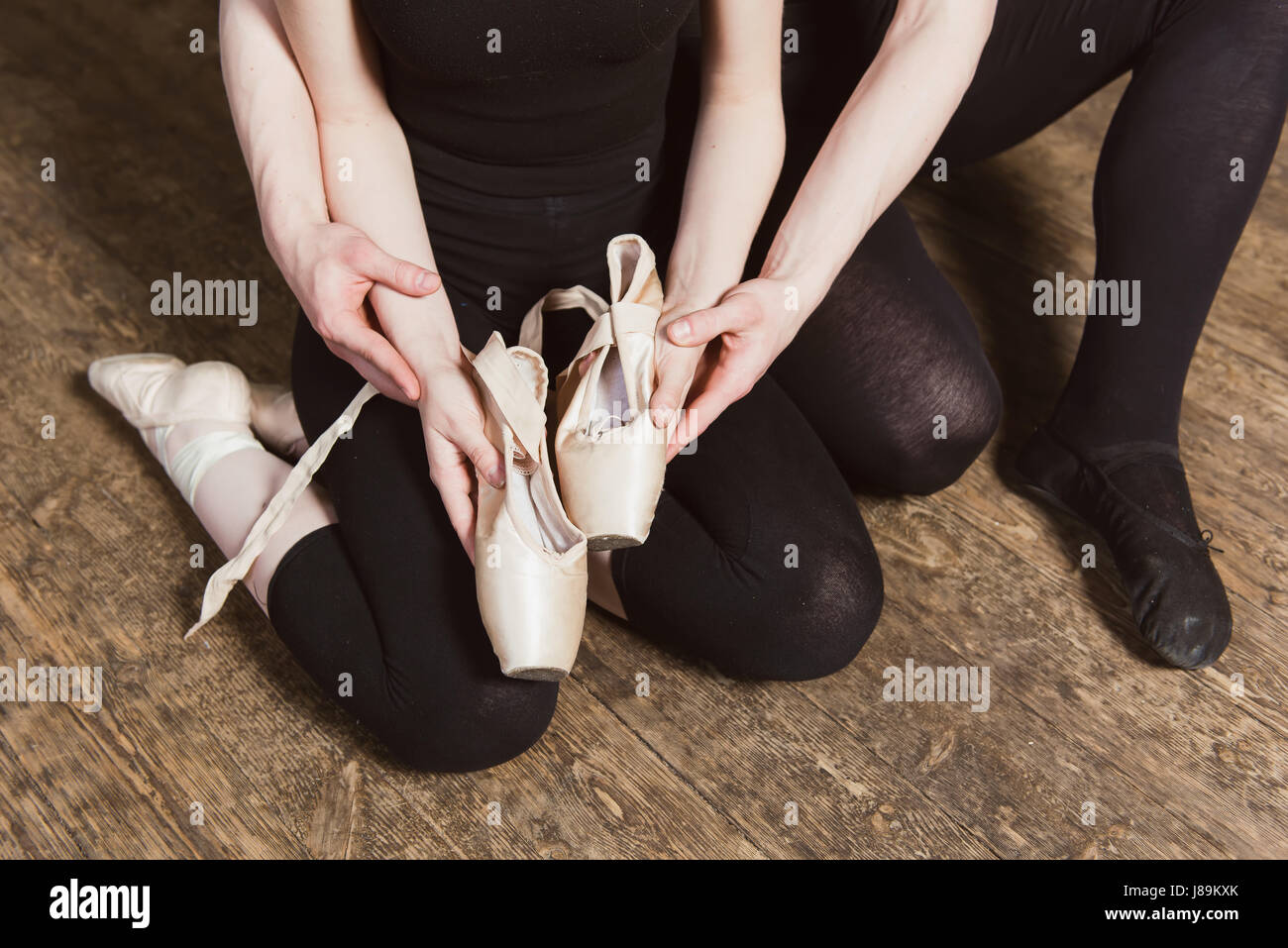 Ballerina and male ballet dancer holding ballet shoes in hands. Top view photo. Horizontal. close-up. - Stock Image