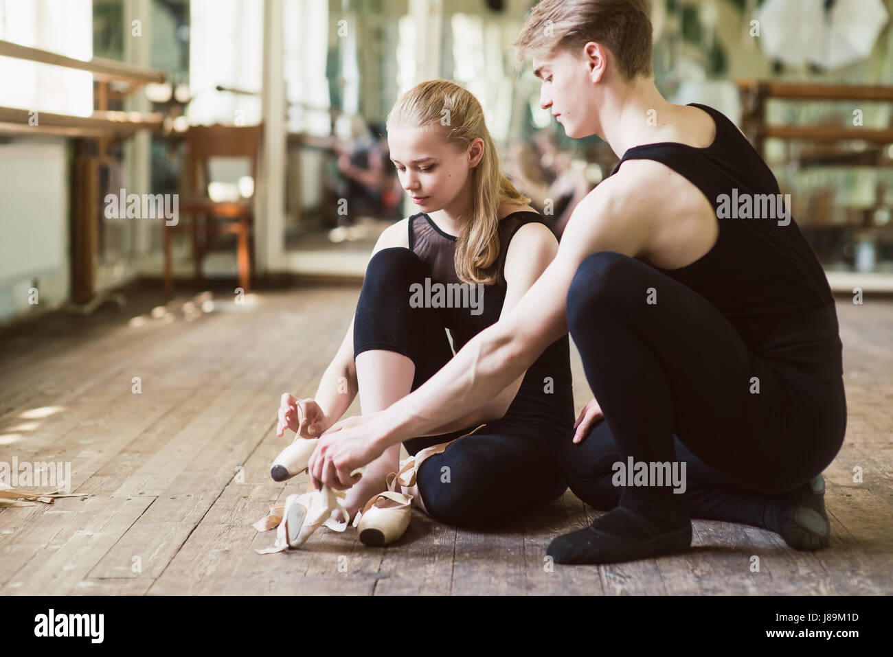 Young ballerina or dancer girl putting on her ballet shoes on the wooden floor. Male ballet dancer helps puttiing - Stock Image