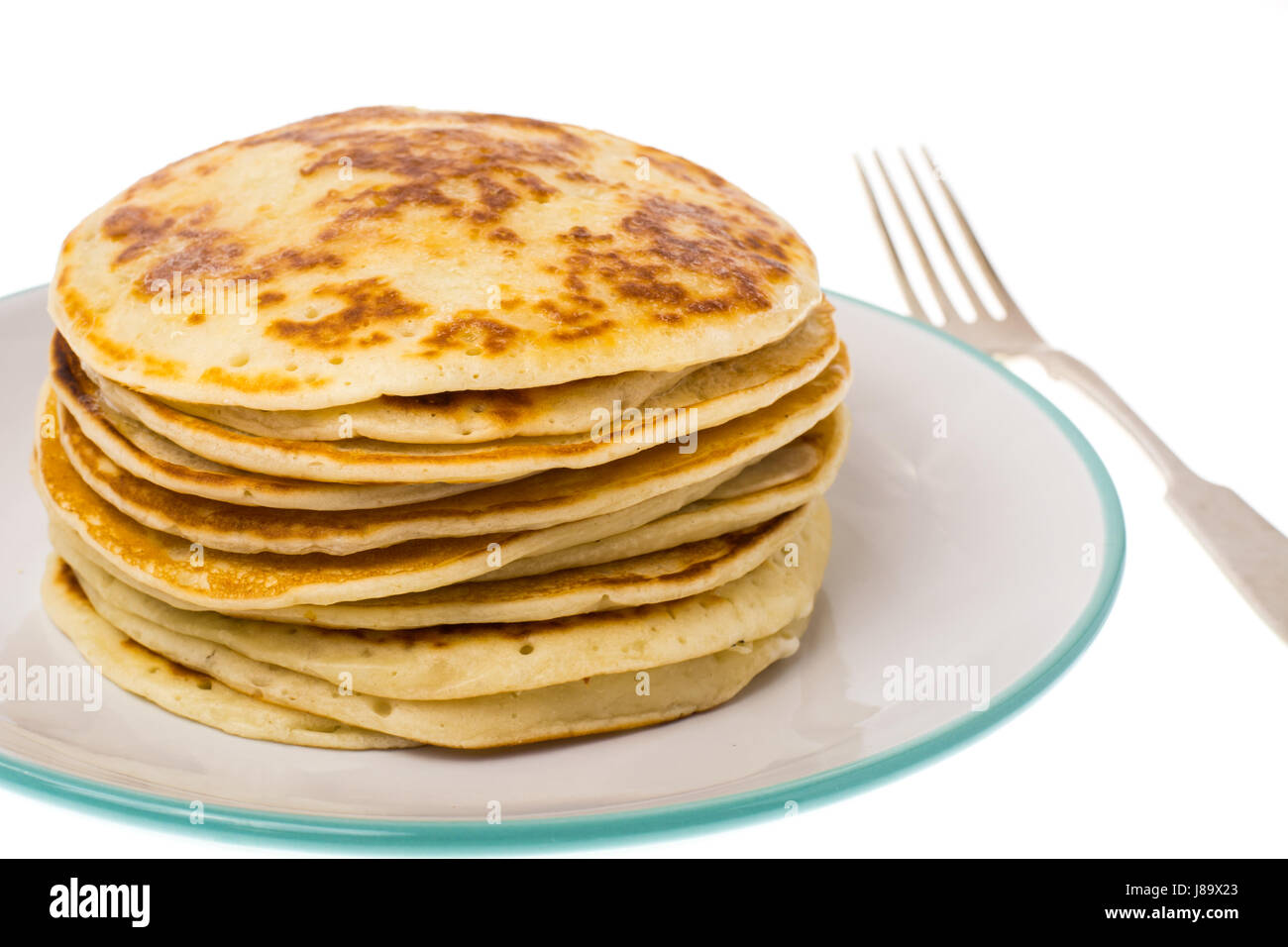 Stack of fried vanilla pancakes on plate on white background - Stock Image