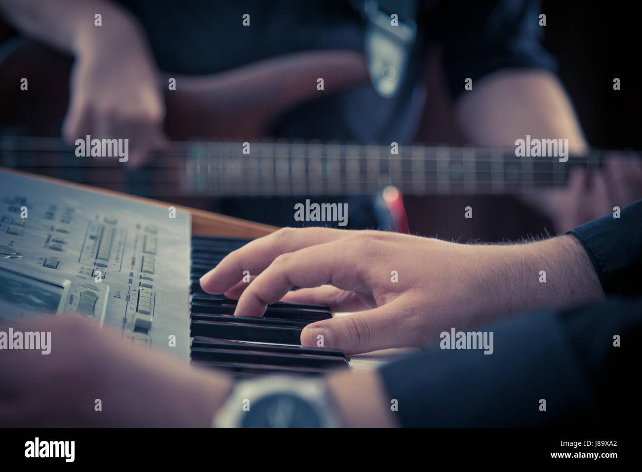 Hand playing music keyboard and bass guitar player in the background. Detail form a concert. - Stock Image