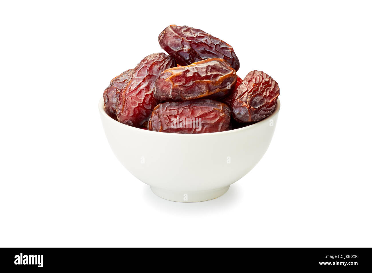 Bowl of dried date fruits on white - Stock Image