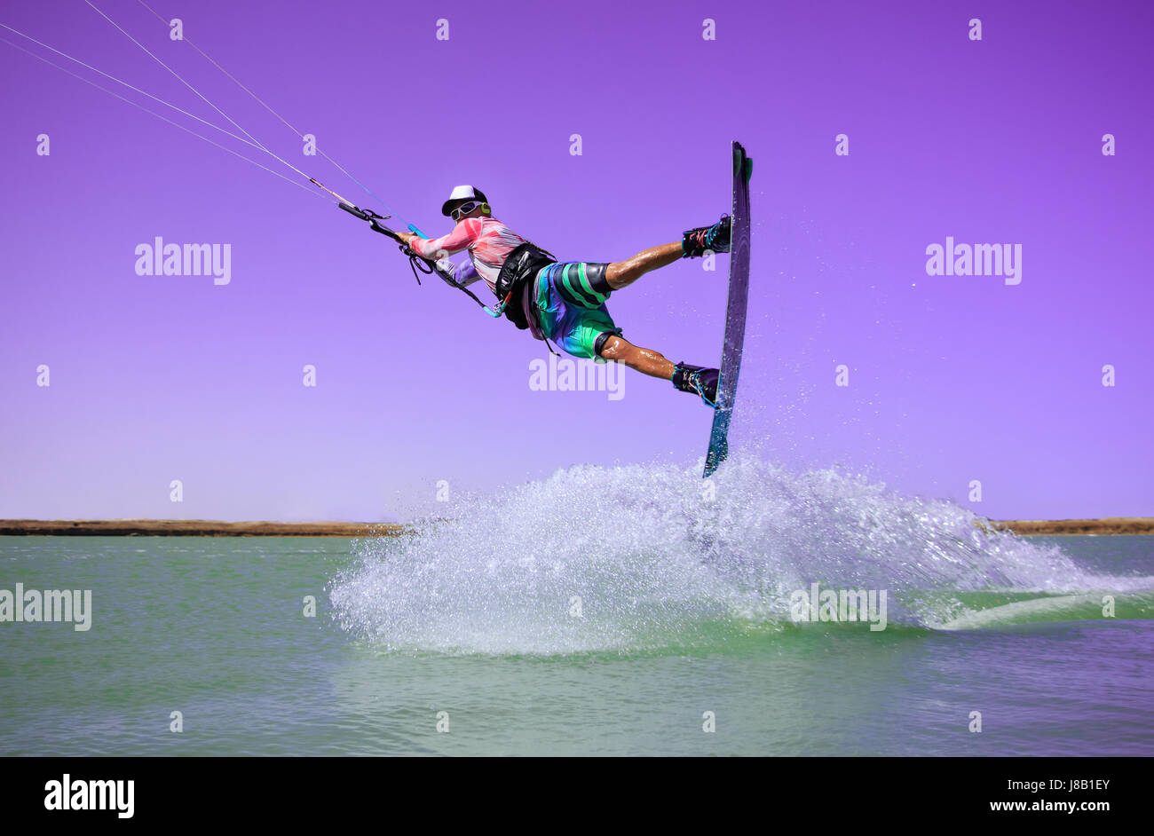 Professional kite boarding rider sportsman jumps high acrobatics kiteboarding raley trick  with huge water splash. - Stock Image