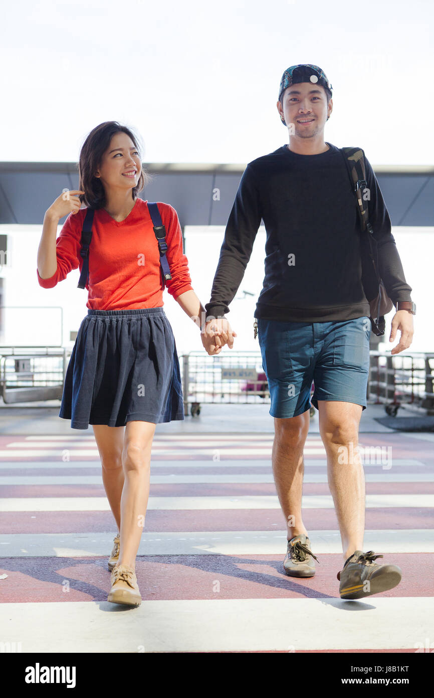 couples asian younger man and woman hand by hand walking with happiness and relax emotion - Stock Image