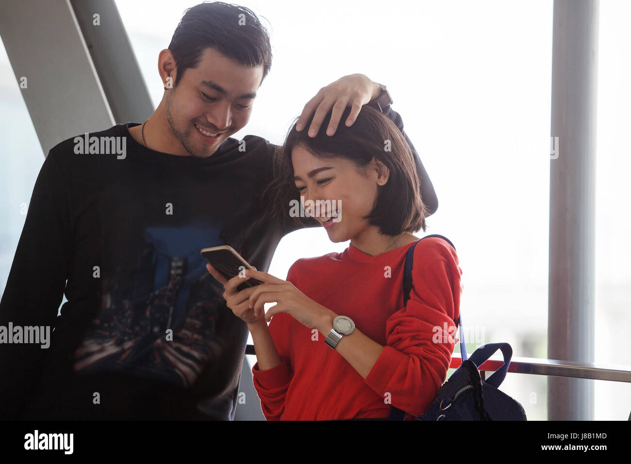 couples of younger asian man and woman relaxing with happy face reading text on smart phone use for people and modern - Stock Image