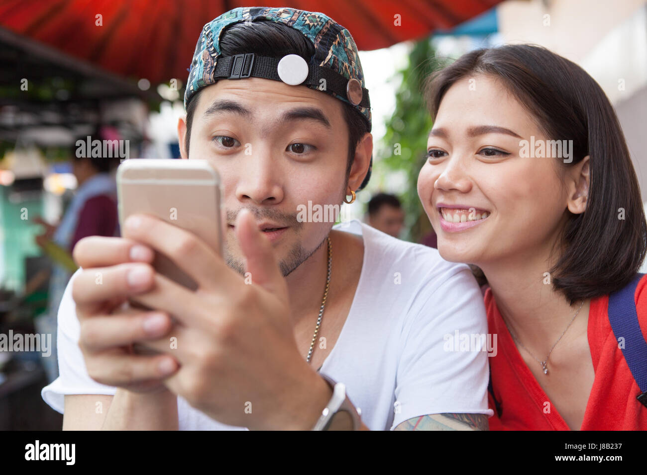 asian younger man and woman watching on smart phone use for people and digital technology ,wifi and internet connection - Stock Image