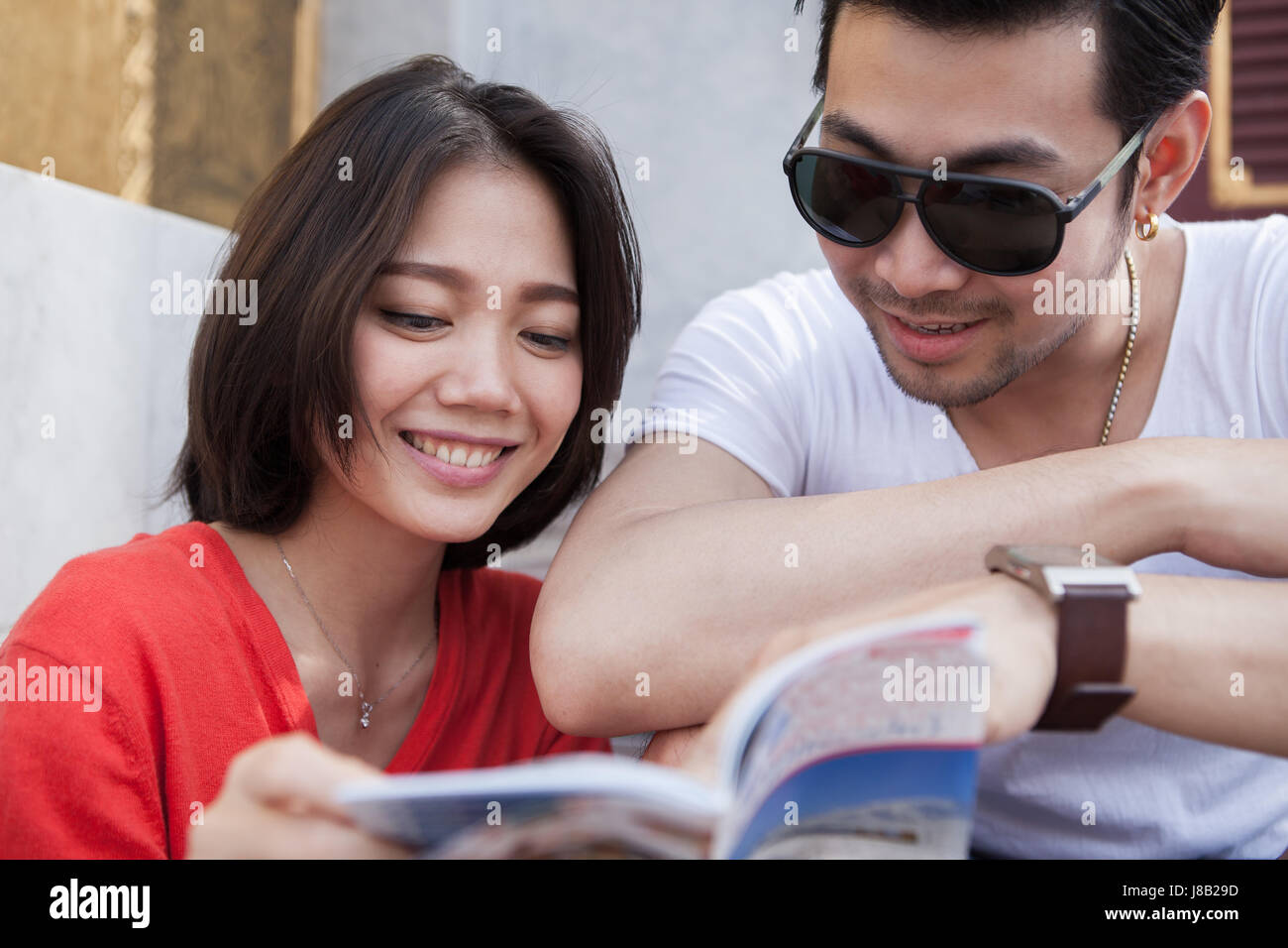 couples of asian younger traveling man and woman reading a guide book with happiness face toothy smile - Stock Image