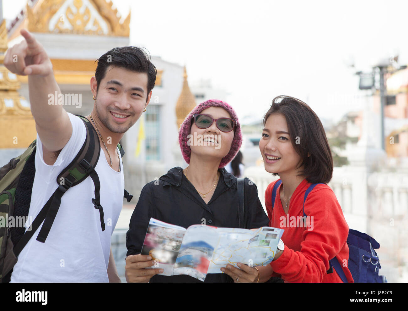 traveling man woman and senior tourist holding travel guide book in hand pointing to destination for visiting - Stock Image
