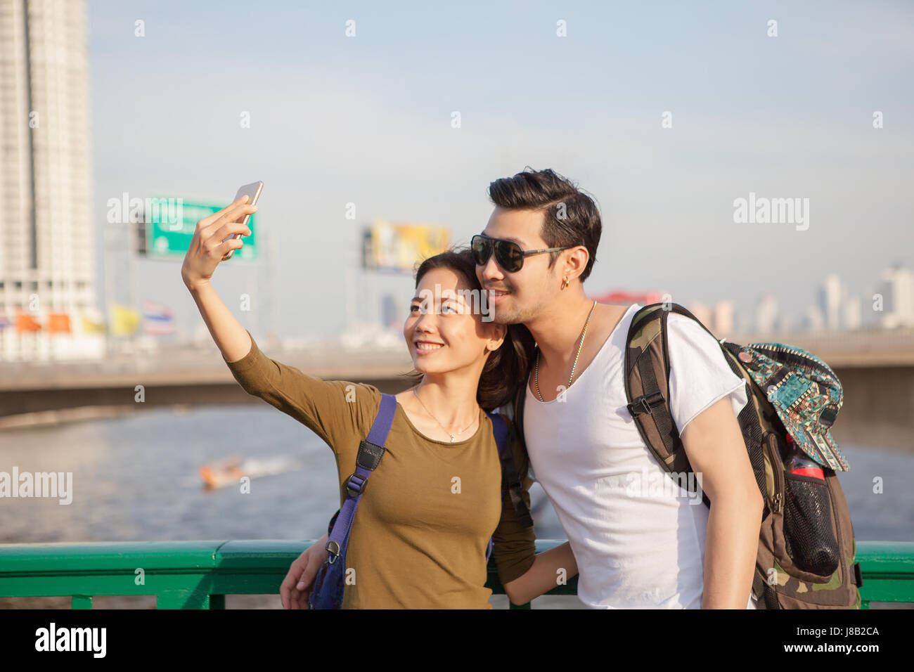 couples of younger man and woman take a selfie photograph by smart phone on traveling location - Stock Image