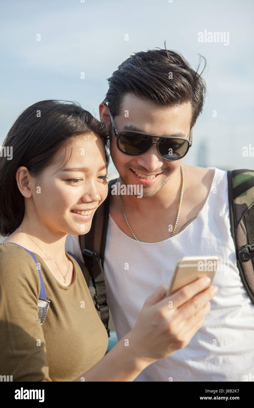 close up face of younger asian man and woman looking to smart phone use for young people digital techmology lifestyle - Stock Image