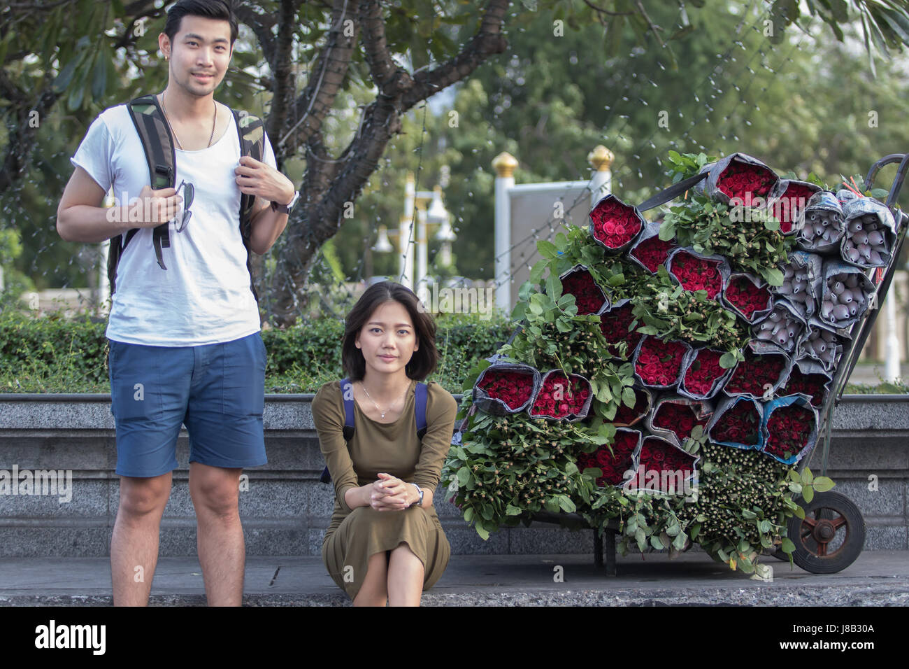 portrait couples of younger asian traveling man and woman sitting at road side beside red roses flower bouquet - Stock Image