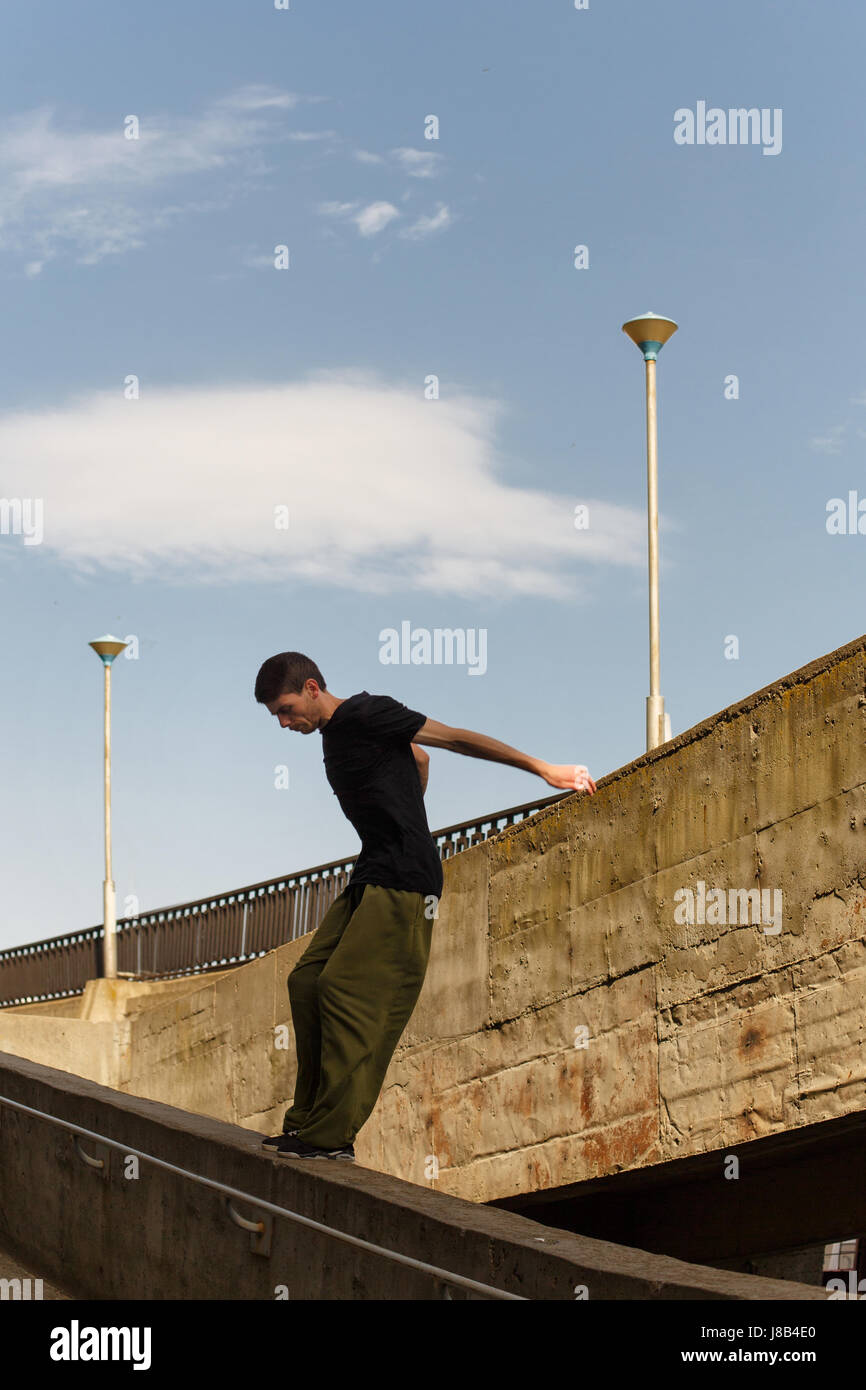 A young man is jumping from a high wall. Parkour in the urban space. Sport in the city. Sport Activities outdoors. - Stock Image