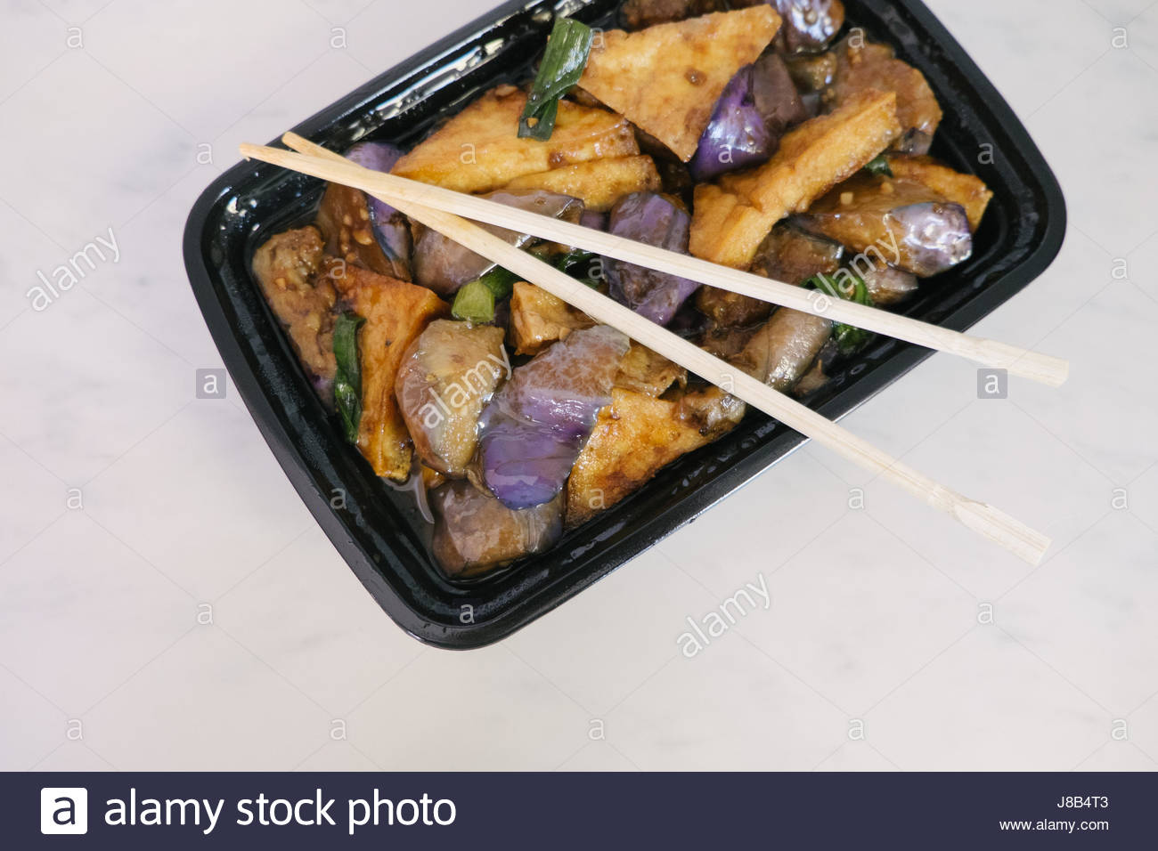 Vegan Chinese food take out on a white marble kitchen counter with stir fried tofu and eggplants. - Stock Image