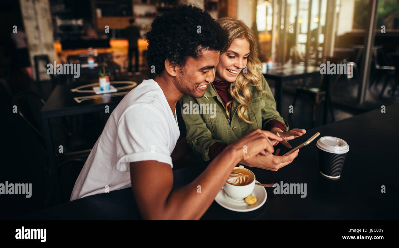 Shot of happy young man with his female friend sitting together at cafe and using mobile phone. Best friends at - Stock Image