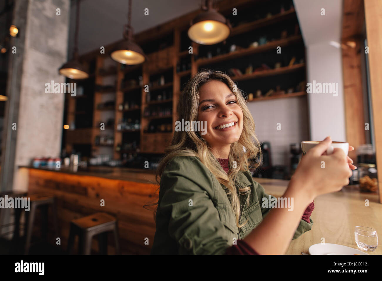 Portrait of beautiful young woman sitting at cafe with cup of coffee and smiling. Caucasian female having coffee - Stock Image