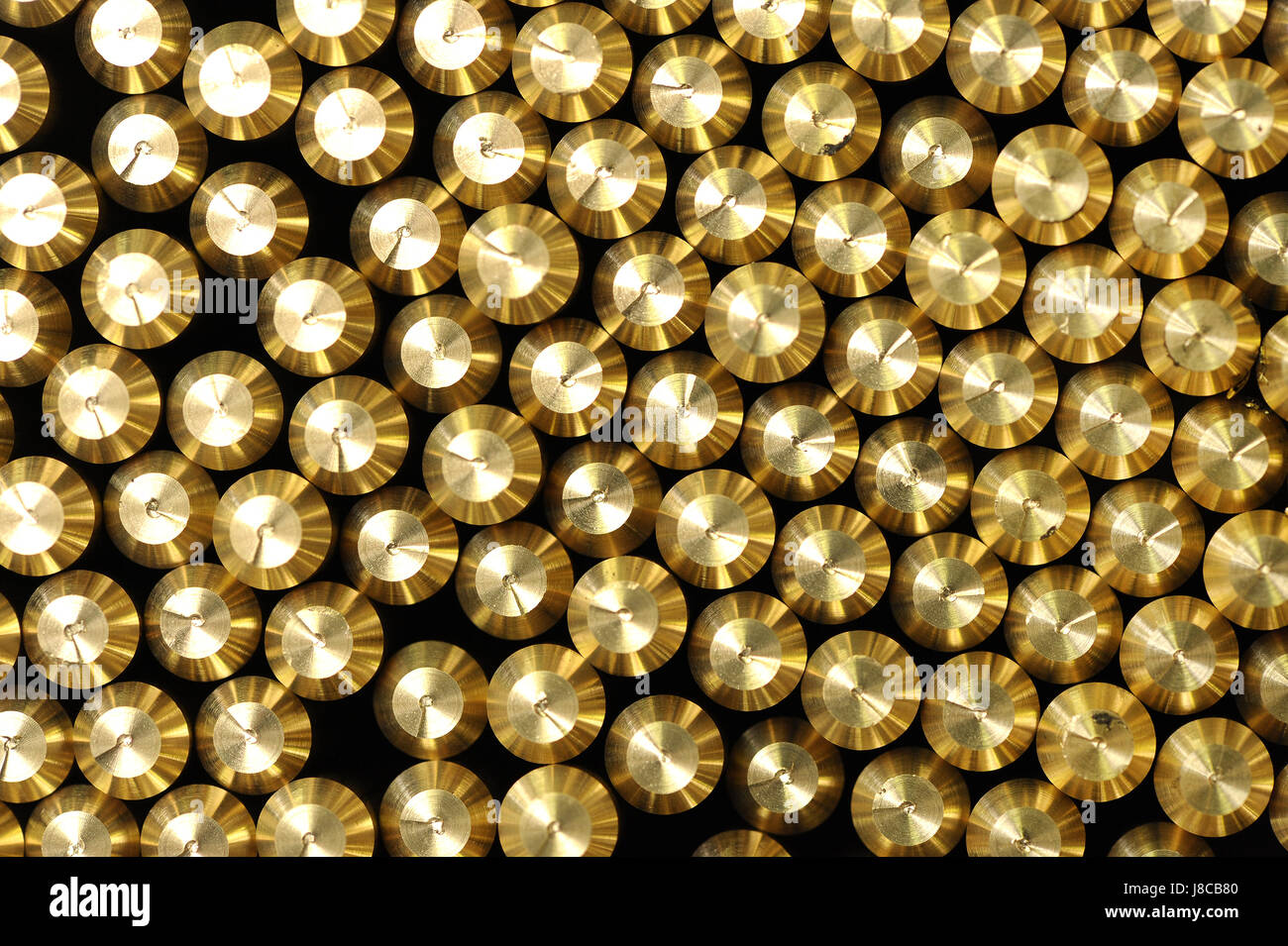 Background pattern of the ends of shiny bevelled brass rods for use as a raw material in industry viewed from above - Stock Image