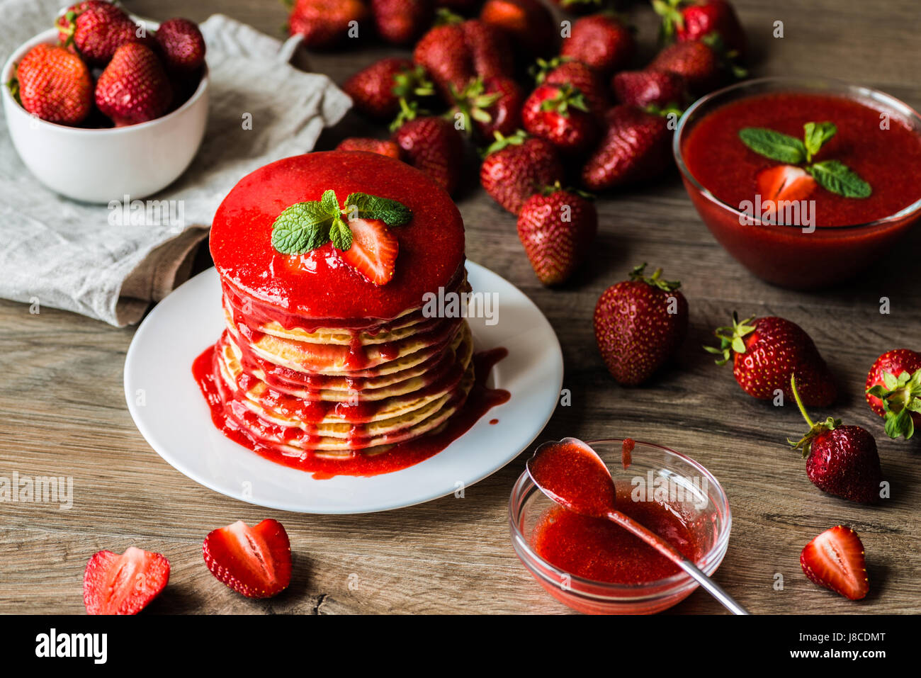 American pancakes and strawberry sauce and bowel with a berry on a wooden background. Shallow depth of field. - Stock Image