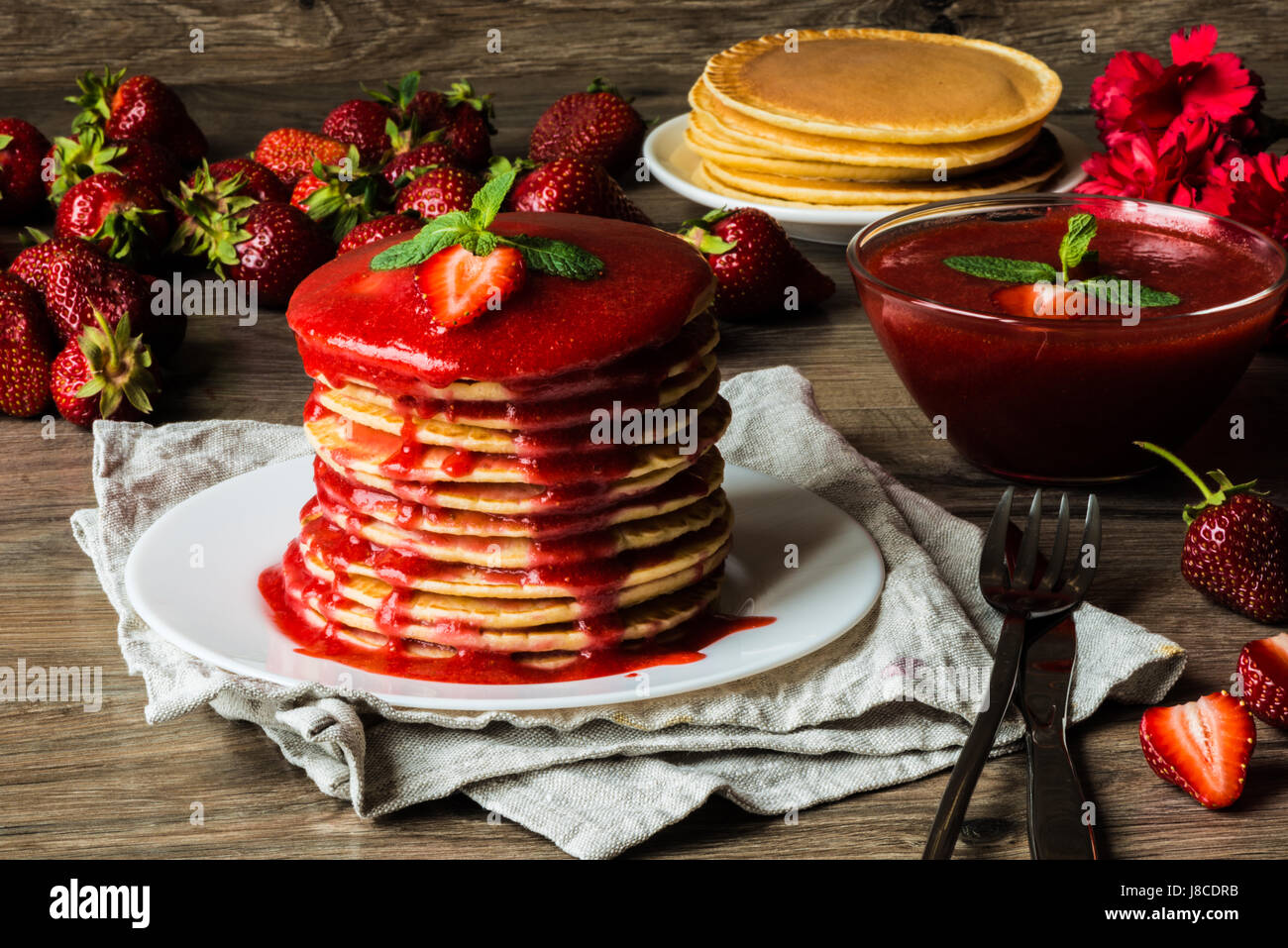 American pancakes and strawberry sauce on a wooden background. Great depth of field. - Stock Image