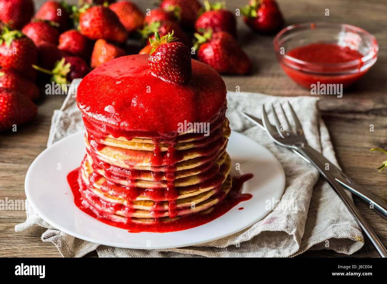 Macro american pancakes with strawberry jam on a wooden background. Shallow depth of field. - Stock Image