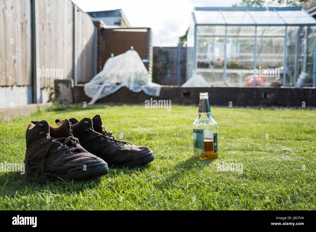 A pair of water soaked brown boots next to an open bottle of beer on a hot sunny day. After a hard day's work - Stock Image