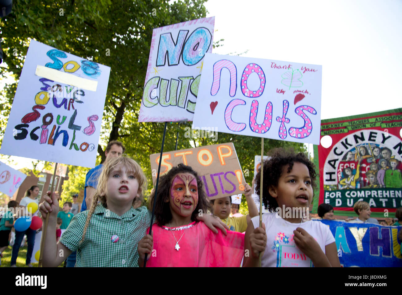 Protest against government plans to cut over 600 teachers in Hackney. Three girls hold placards saying 'No cuts' - Stock Image