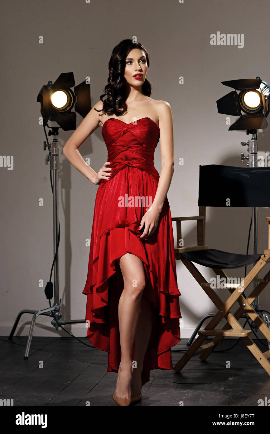 Young pretty beautiful woman in red long evening dress with makeup ...