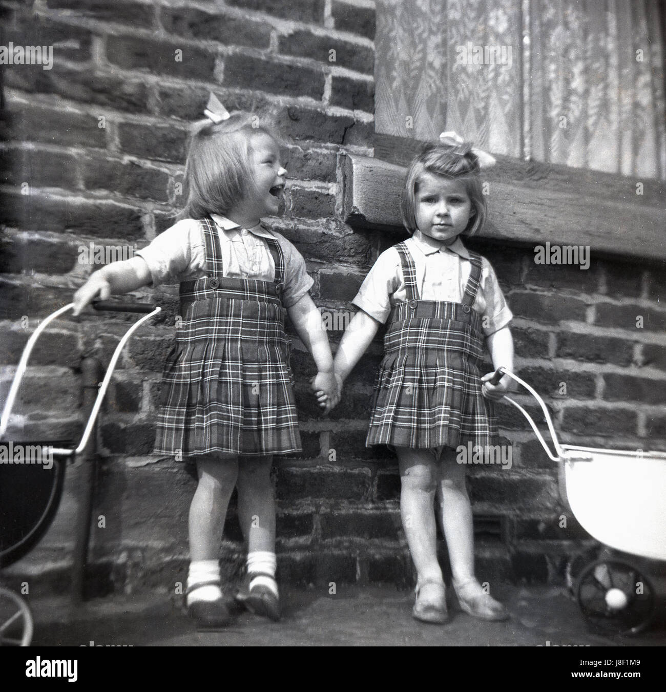 c8145da142ec 1950s, historical, two little girls, sisters, wearing matching tartan  dresses with their toy doll prams outside a brick house, one laughing,  holding hands.