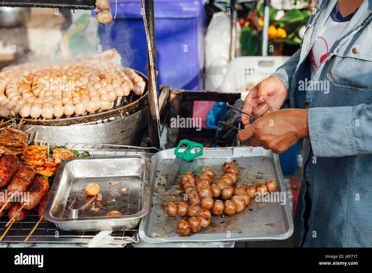 CHIANG MAI, THAILAND - AUGUST 21: Thai woman cooks meatballs at the Sunday Market (Walking Street) on August 21, - Stock Image