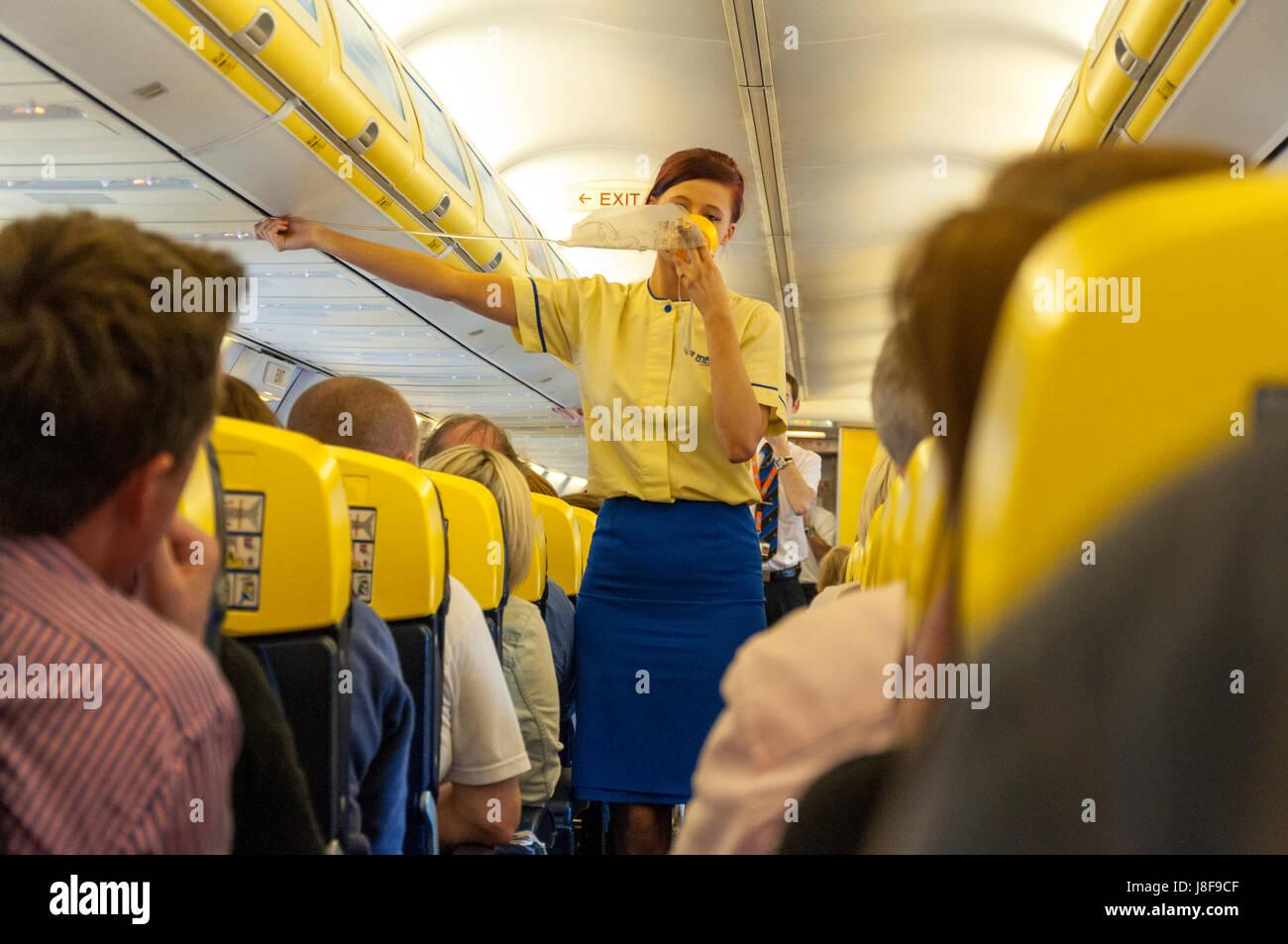 Flight safety demonstration aboard a Ryanair flight. Attendant demonstrates oxygen mask - Stock Image