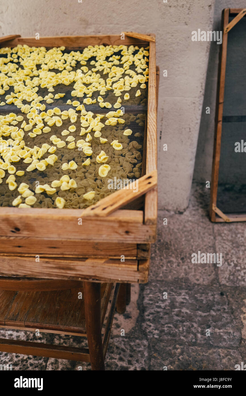 Handmade Orecchiette pasta drying in the streets of Bari Vecchia, Puglia, Italy - Stock Image