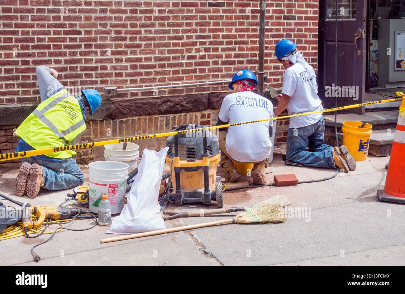 Three men repairing and restoring the red brick outside wall of a building in Lower Manhattan - Stock Image