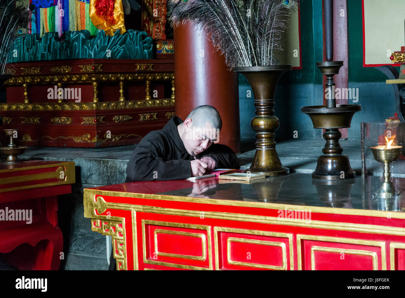 Monk writing, Lama Temple, Buddhist temple and monastery, Dongcheng District, Beijing, China - Stock Image