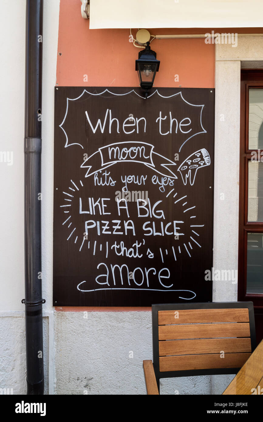 Lyrics from Dean Martin's hit That's Amore written on a chalkboard outside of pizzeria in Piran, Slovenia - Stock Image