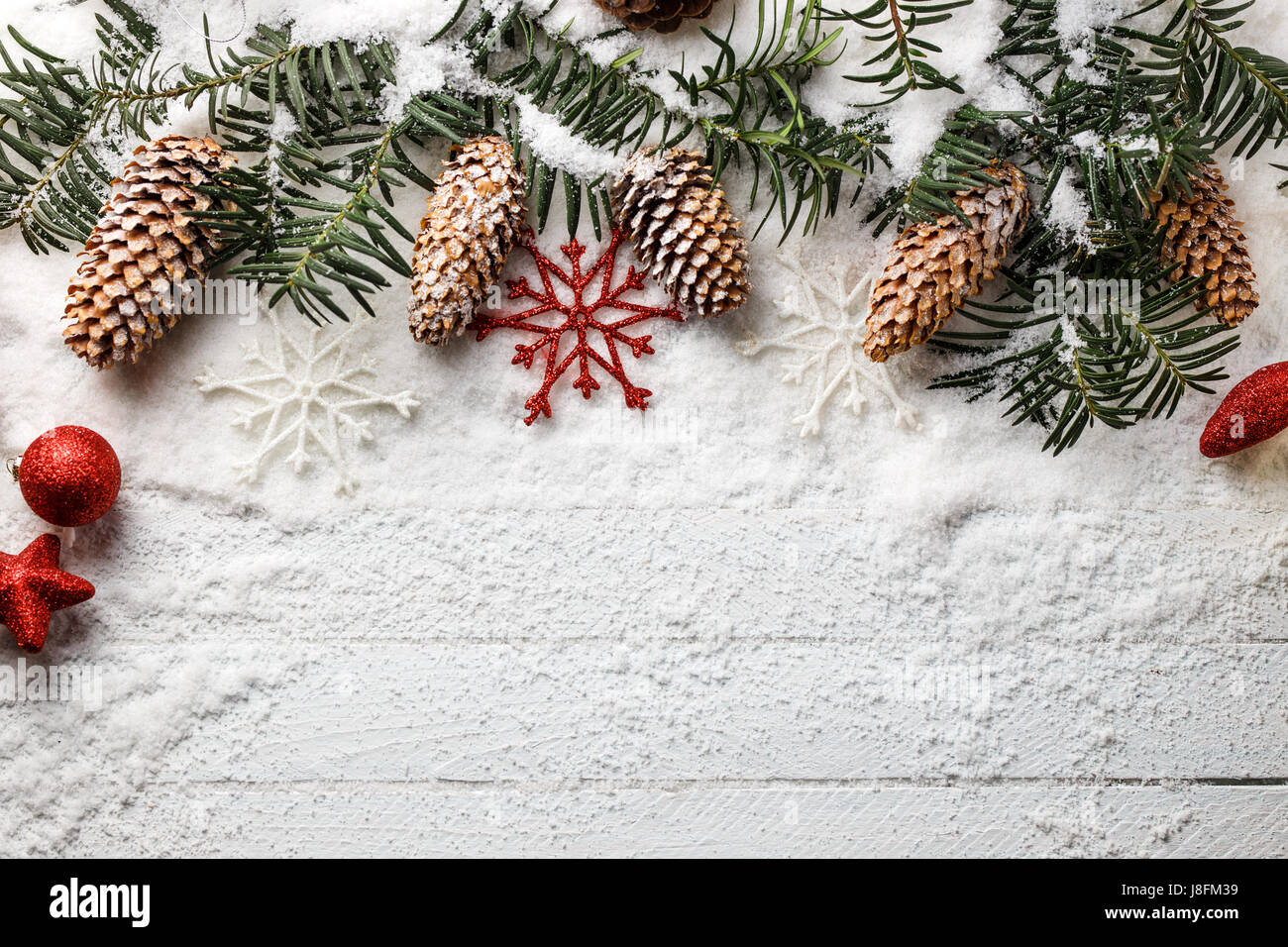 snowy christmas background with fir branch and pine cones J8FM39