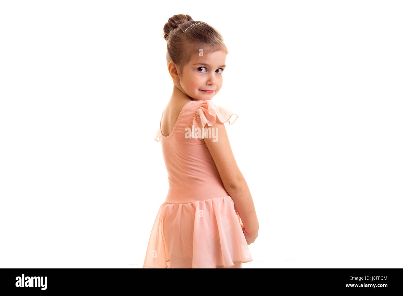 187cbf86881c Sad little girl in pink dress with bundle dancing on white background in  studio