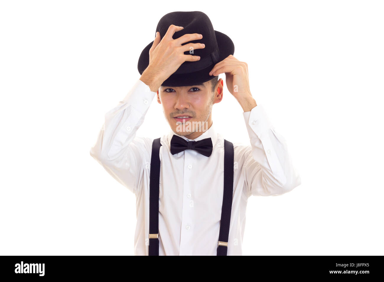 35960c8d9609 Elegant young man in white shirt with black bow-tie, suspenders and hat on