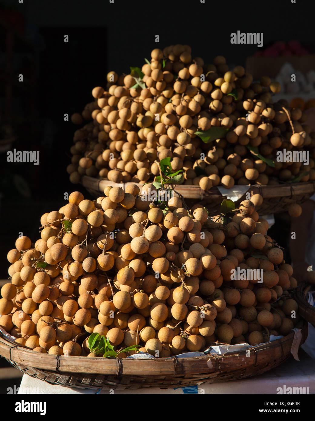 Baskets full of tropical longan fruit under morning light at the street market, Vietnam. - Stock Image
