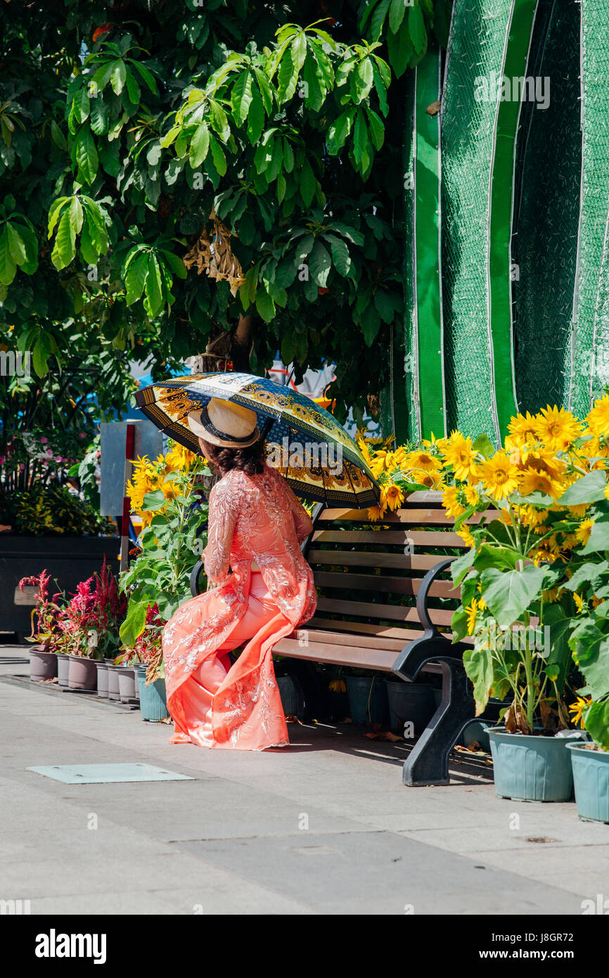 Ho Chi Minh City, Vietnam - February 07, 2016: Woman with umbrella in Ao Dai dress poses for picture during flower - Stock Image