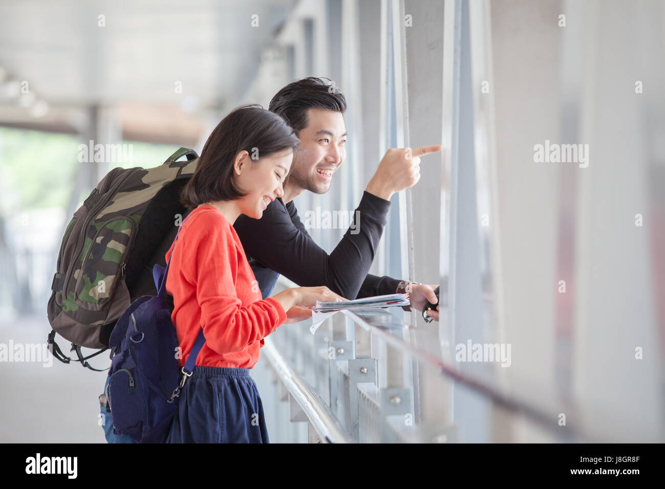 couples of younger traveling man and woman looking to traveler guide book on location - Stock Image