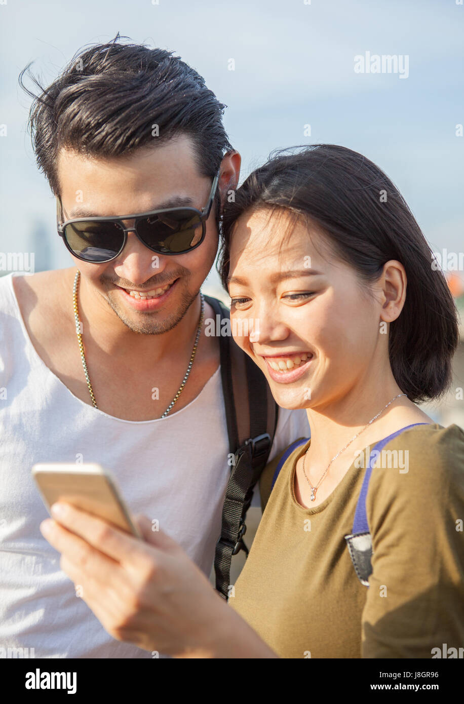 close up face of younger asian man and woman looking to smart phone use for young people digital technology lifestyle - Stock Image