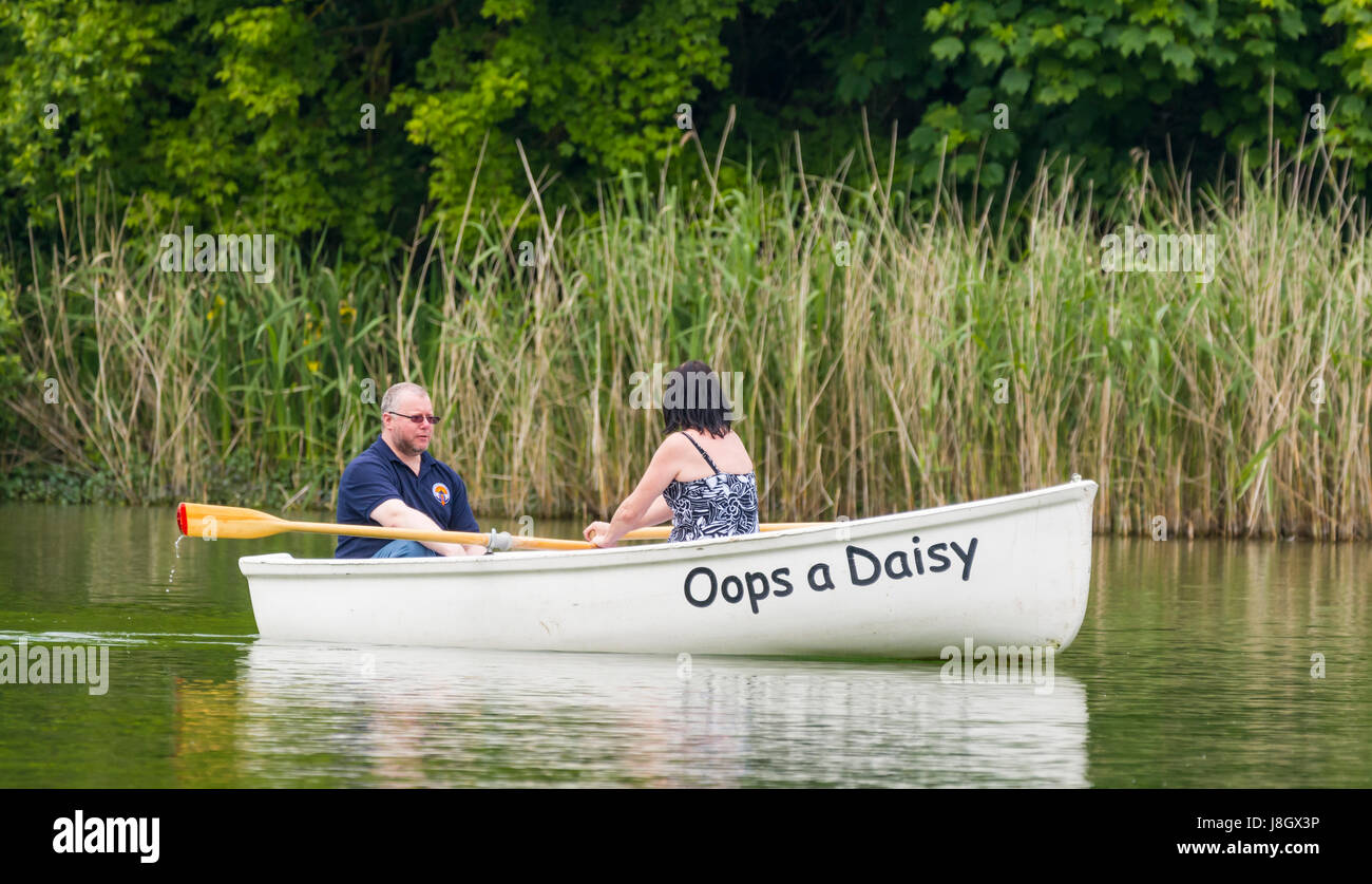 Couple in a small wooden rowing boat on a boating lake in Spring. - Stock Image
