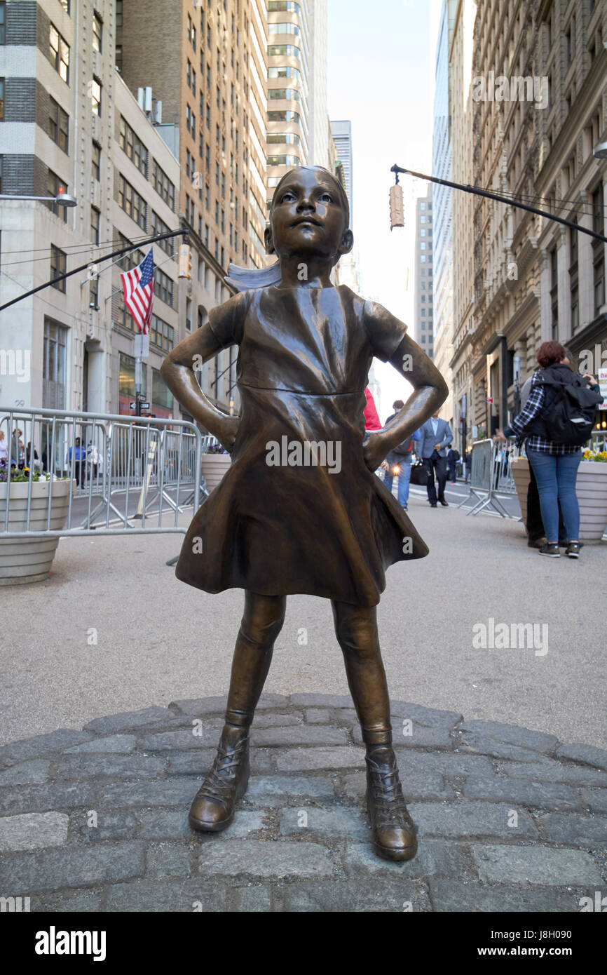 Fearless girl sculpture facing charging bull New York City public art bowling green broadway USA - Stock Image