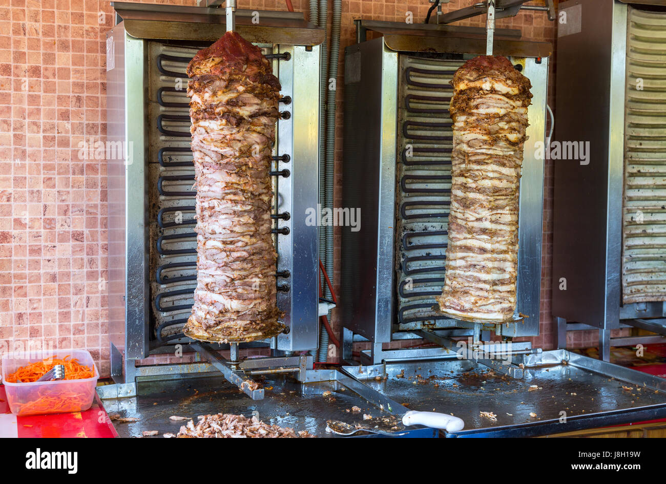Traditional fast food Turkish doner kebab meat on a rotary grill - Stock Image