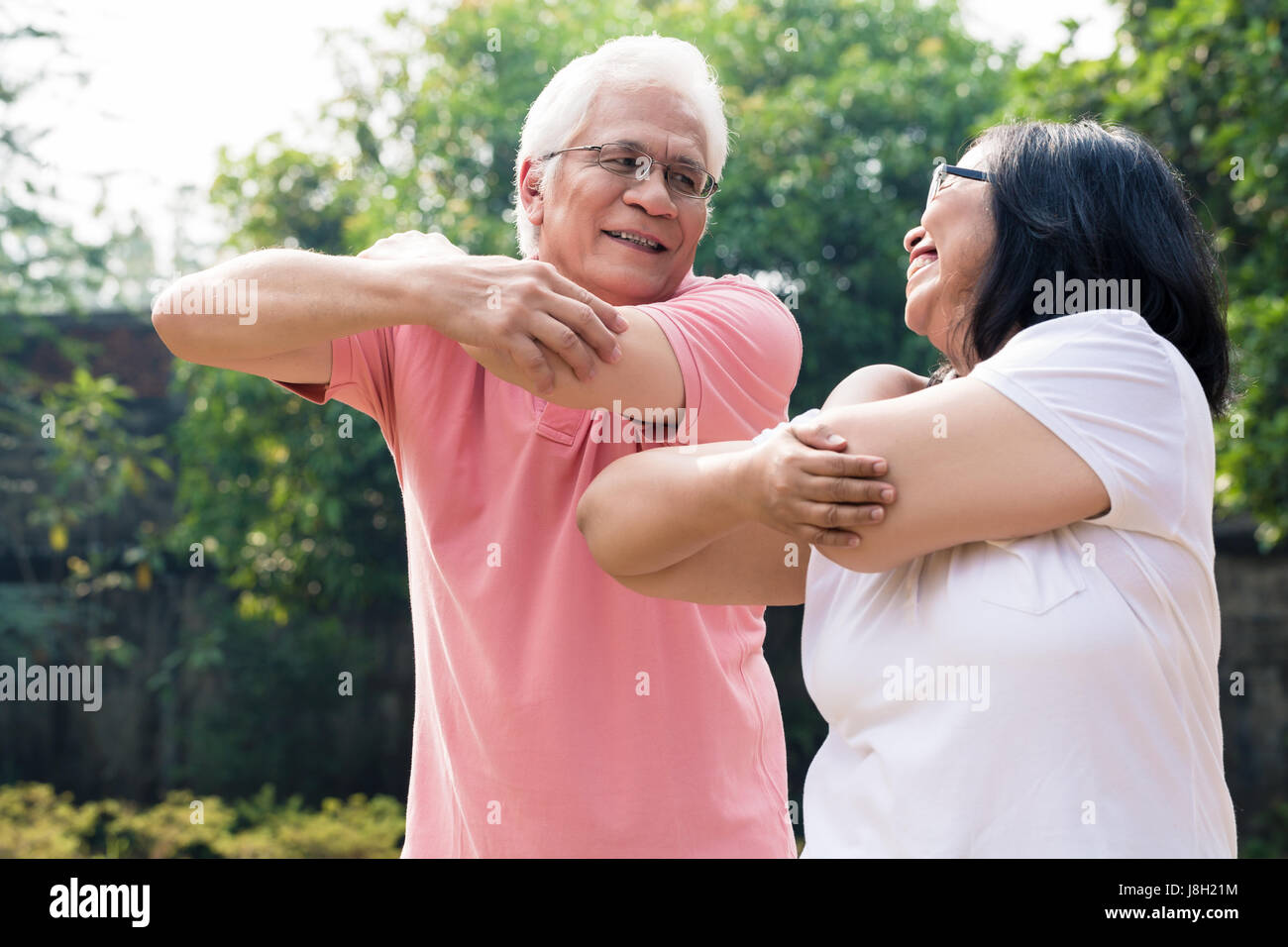 Senior man assisting his wife during warming up exercises outdoo - Stock Image