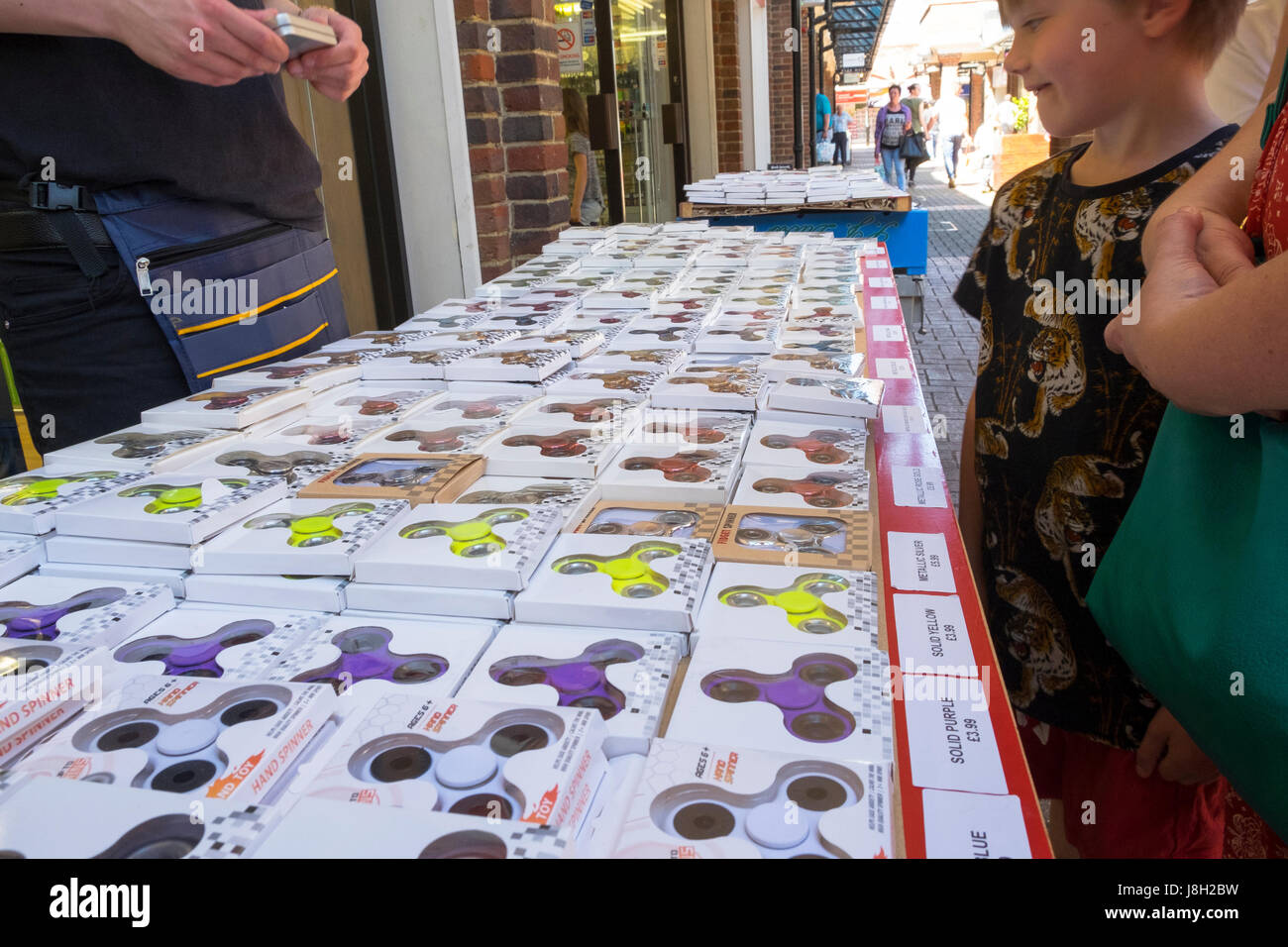 Fidget spinners the latest craze to hit the UK, various colours market stall young boy buying - Stock Image