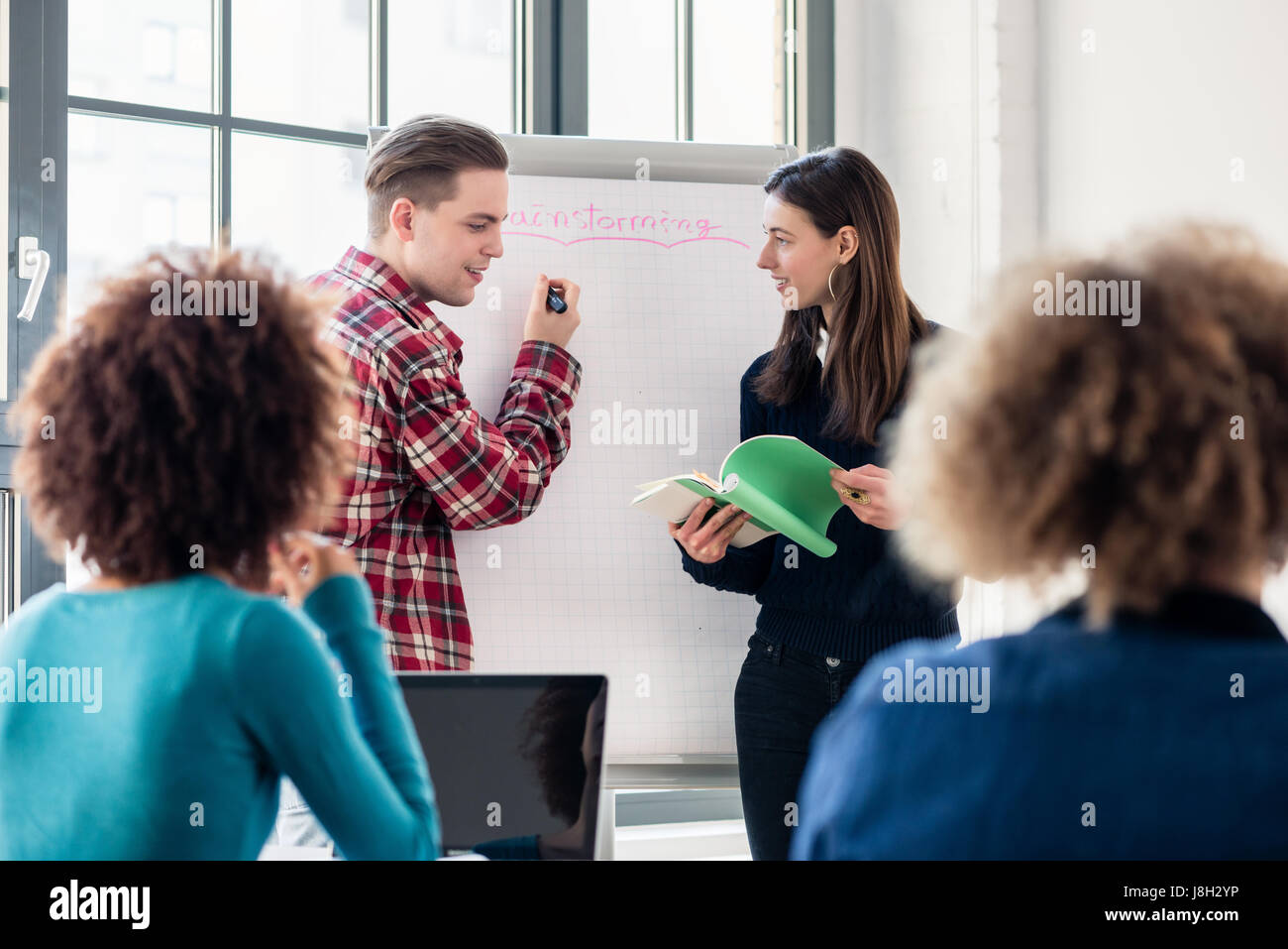 Students sharing ideas and opinions while brainstorming during a - Stock Image