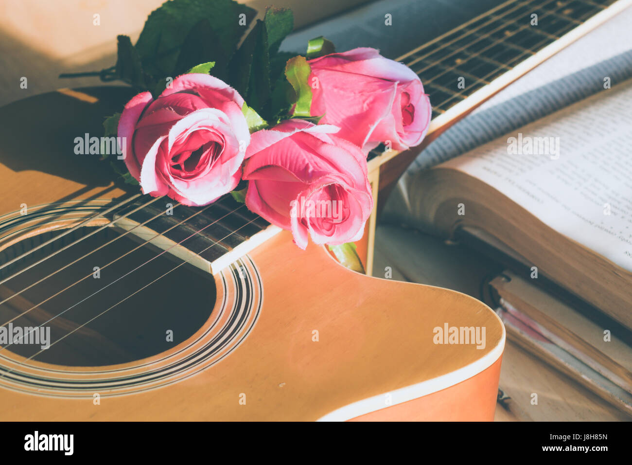 Rose flowers on a book with a guitar on a wood table. - Stock Image