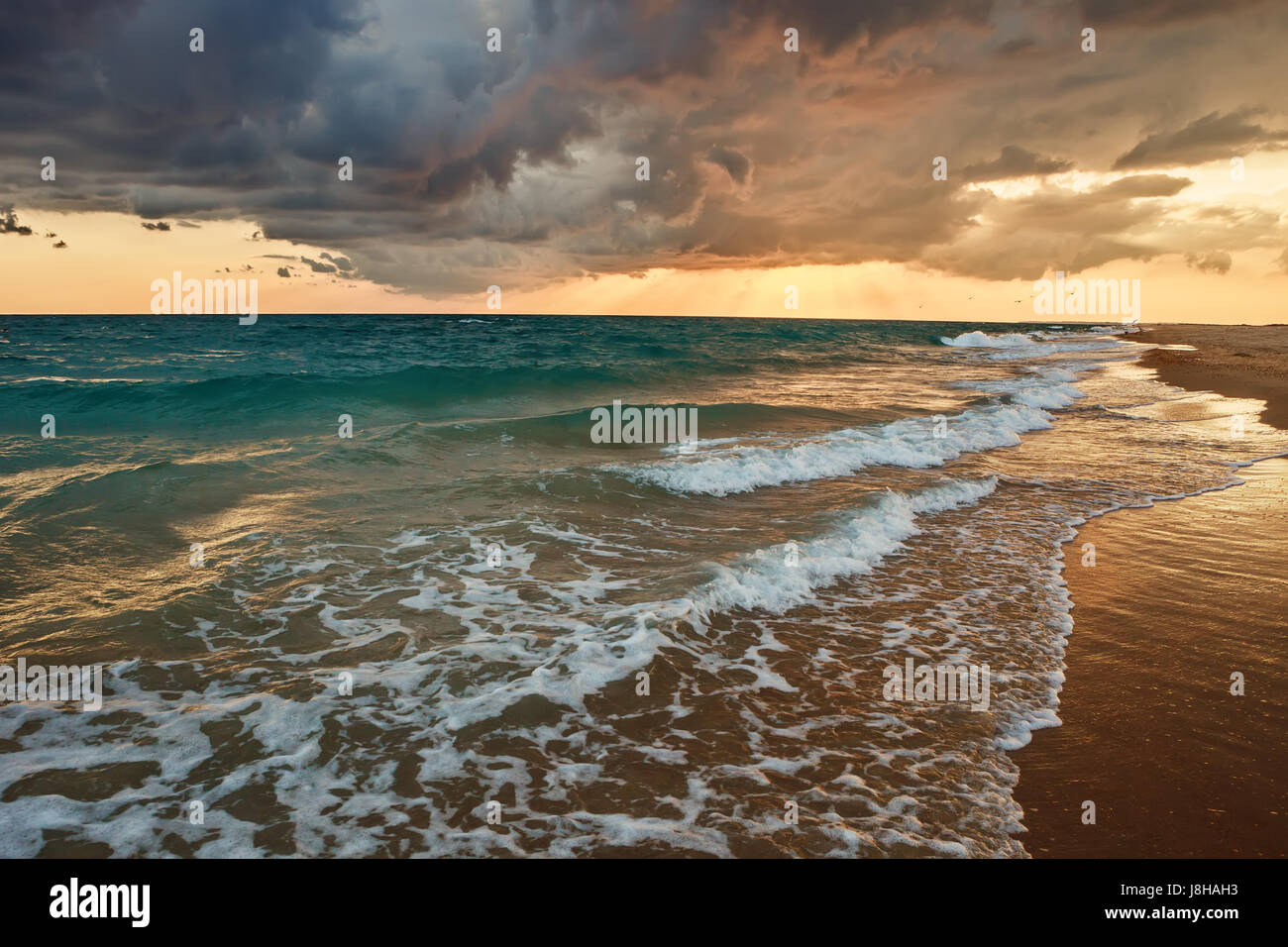 Fiery orange sunset sky. Beautiful sky.Beautiful flaming orange sunset with dark clouds above the sea. - Stock Image