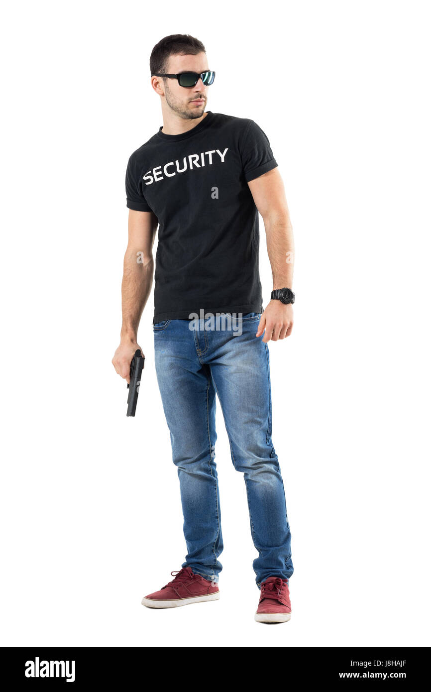 Cautious young undercover cop with sunglasses holding gun looking