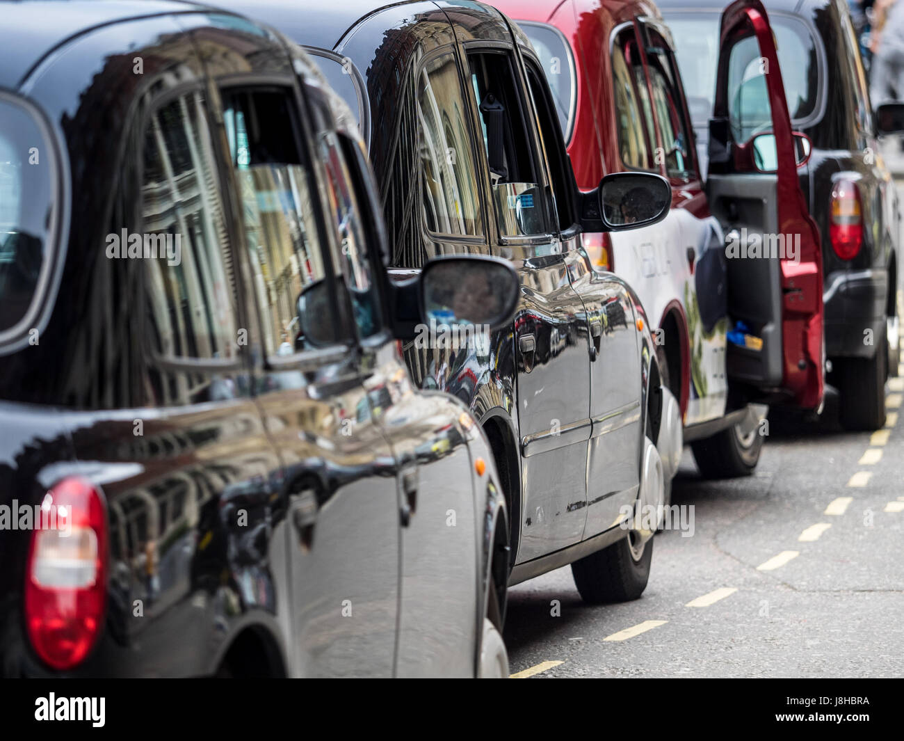 London Taxis Black Cabs queue for passengers at a Central London Railway Station Stock Photo
